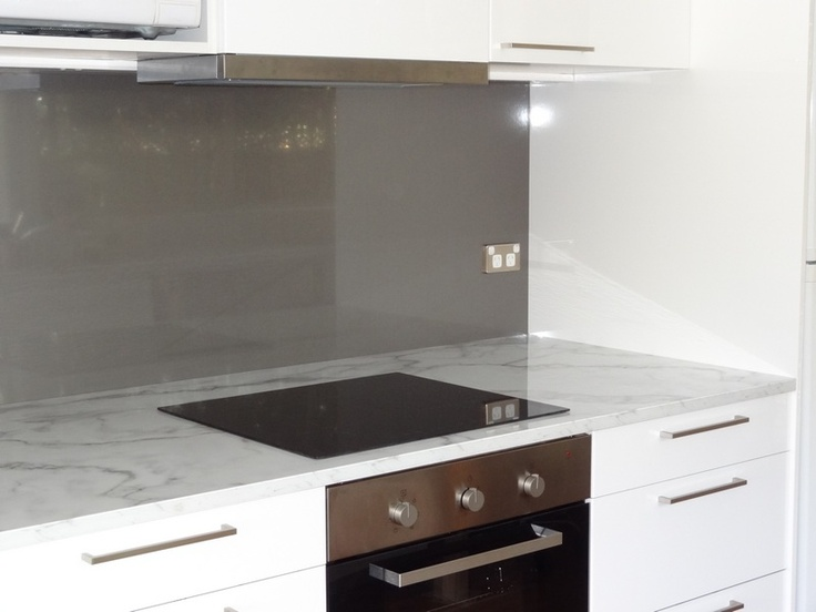 Countertops and oven with white cabinetry and feature black cabinetry directly above oven