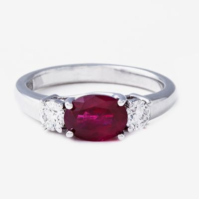 Centre stone is a 1.60ct oval cut ruby with 2 = 0.40ct GH/VS – SI round brilliant cut diamonds set in an 18k white gold trilogy design
