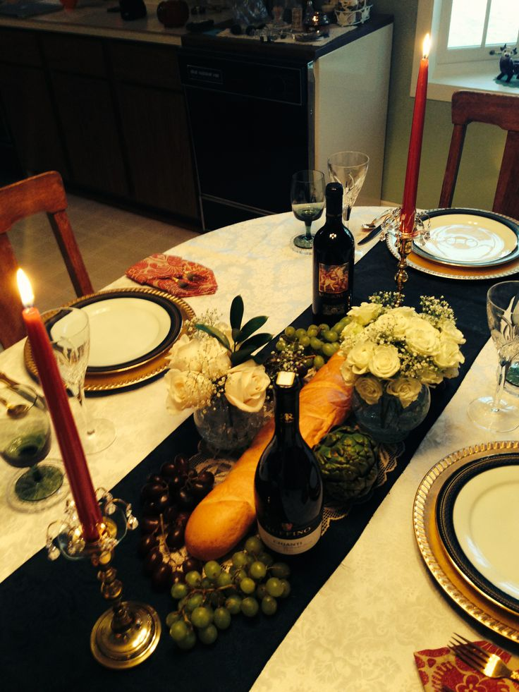 Italian dinner centerpiece. Fresh loaf of bread, green ...