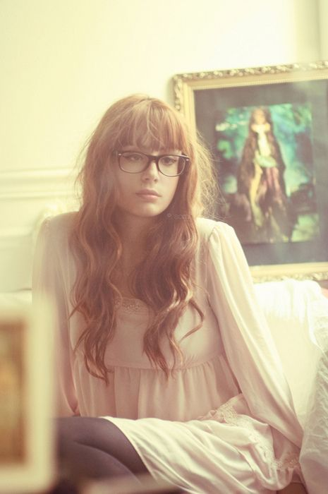 Long wavy brown hair with straight across bangs and big glasses                                                                                                                                                                                 More