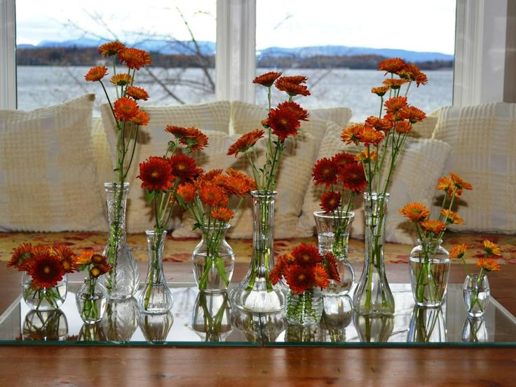 Create a wow factor with a clear and reflective monochromatic color scheme. Lay a mirrored runner on the table. Gather together a bunch of clear glass vessels, and fill each one with flowers of the same color.  We spent less than $10 at the second-hand store for the vases and less than $10 for the flowers.