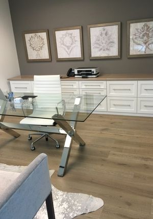Feminine office remodel: Glass top desk; storage; framed art; Herman Miller high-back white leather chair; rug | Interior Designer: Carla Aston