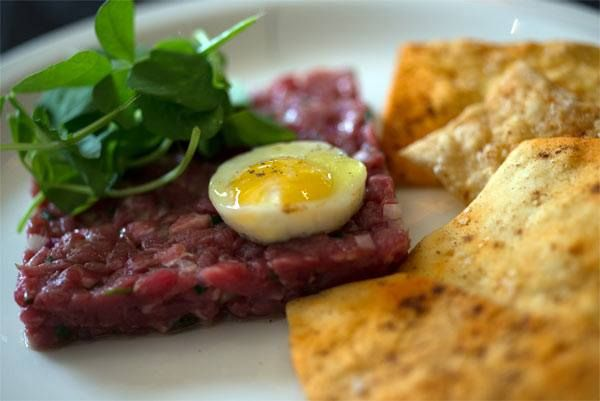 beef tartare swank farms sorrel, worcestershire vinaigrette and a fried quail egg