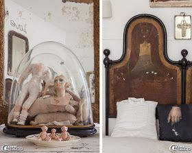 Morceaux de poupées en porcelaine enfermés dans un globe de mariée, collection de petits cochons en porcelaine chinés à Carpentras, tête de lit en fer décorée d'un paysage peint provenant d'un lit toscan du XVIIIème siècle, dessus de lit blanc 'AquaVireo', coussin réalisé à partir d'une chemise, création 'Clair de Lune' à Uzès et coussin 'Vox Populi'