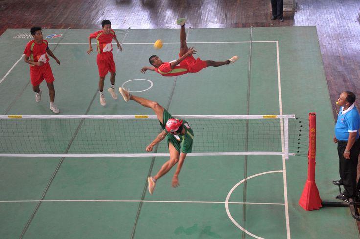 Οι παίκτες του ποδο-βόλεϊ επιδίδονται σε ακροβατικές φιγούρες κατά τη διάρκεια ενός αγώνα του αθλήματος στη Ραγκούν της Μιανμάρ.