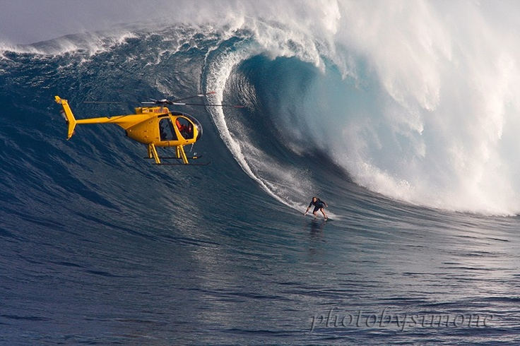 Jaws Maui a monster wave at Peahi surfer riding large wave yellow helicopter.