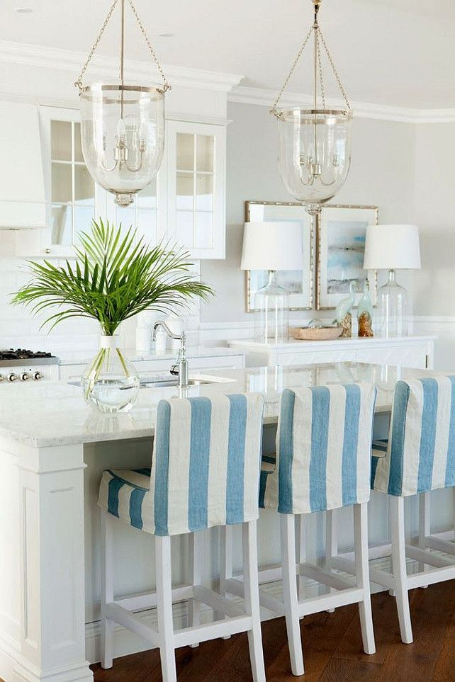 Coastal kitchen with bell jar lantern pendants, strip slicovered barstools, white marble countertop, white cabinets and coastal wall art and coastal decor. #Coastal #Kitchen Verandah House.