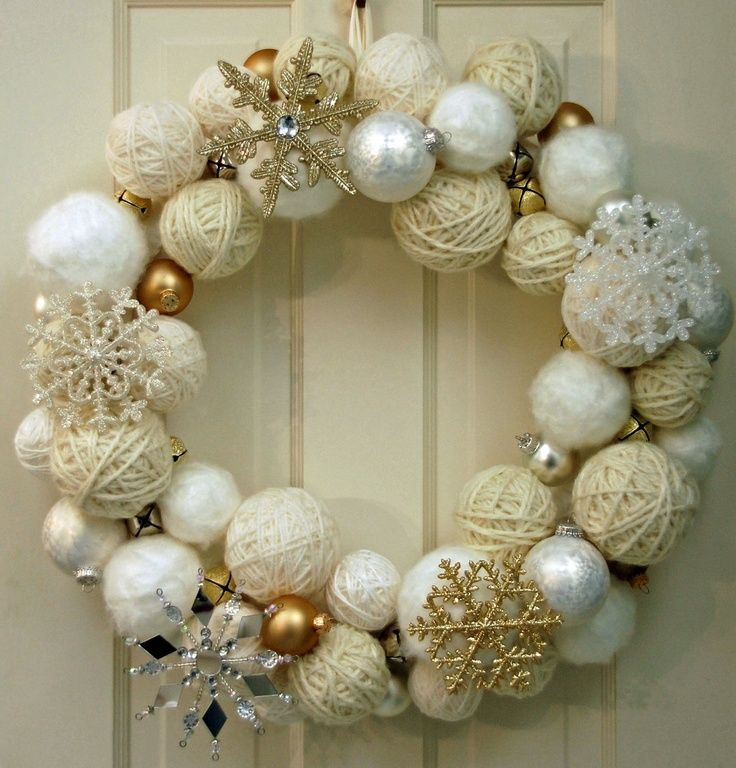 styrofoam wreath covered with white fabric, then adorned with three sizes of styrofoam balls, which are wrapped in various shades of white and off-white yarn. Along with the yarn balls, this wreath is embellished with ornaments and snowflakes in white, silver and gold, as well as gold and silver jingle bells.