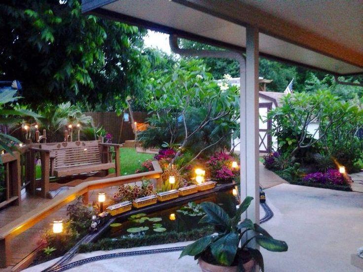 bassin à carpes koi moderne, bornes de jardin et train jouet qui passe au-dessus