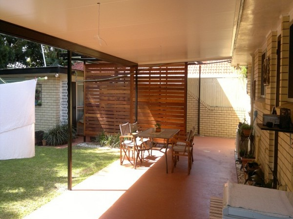 Timber wall under an insulated patio roof
