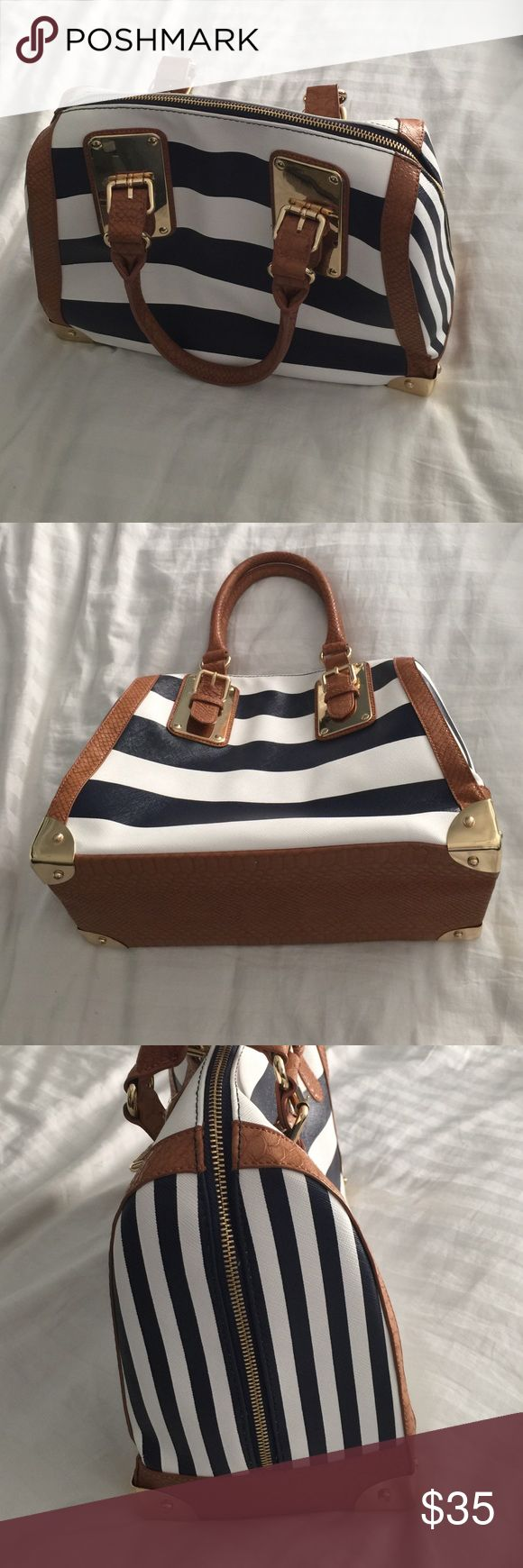 Aldo handbag Beautiful navy/white/tan stripped handbag. Gold details on the buckles and feet. Used 2 times (pre-baby and pre-diaper bag). Inside has a zipper and two side pockets for a phone. Small marking ok the gold feet from being placed on the ground. Faux leather material. Aldo Bags