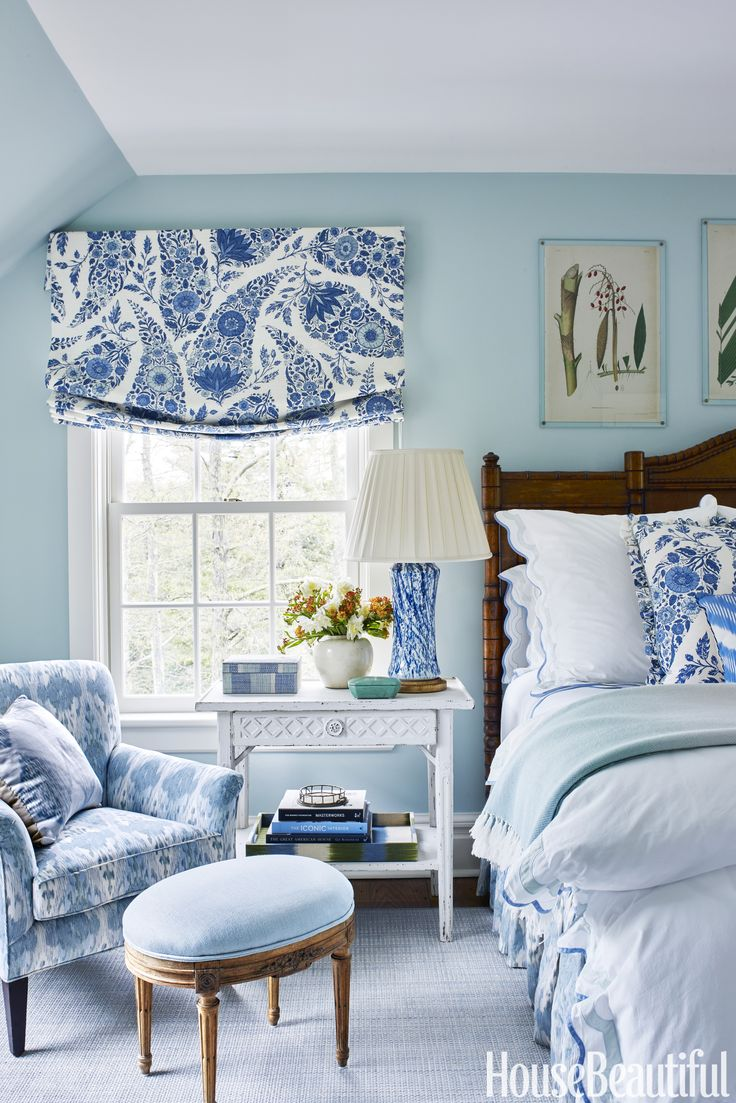 BEDROOM Classic blue and white makes an appearance in the guest bedroom. The Roman shade and matching bed cushion are in a Raoul Textiles silk. The nightstand and lamp are from Bunny Williams Home.