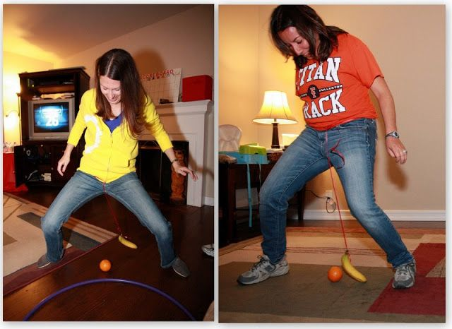 Attach a banana (or something else) on a string around her waist so it dangles above the ground. In 60 seconds, they must move an orange (or a ball) across the room and into a hula hoop using only the banana.