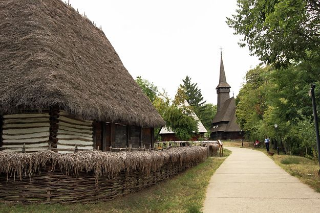 Visit to Bucharest Romania - Old wooden house and church from Maramures county, on display at Dimitrie Gusti National Village Museum