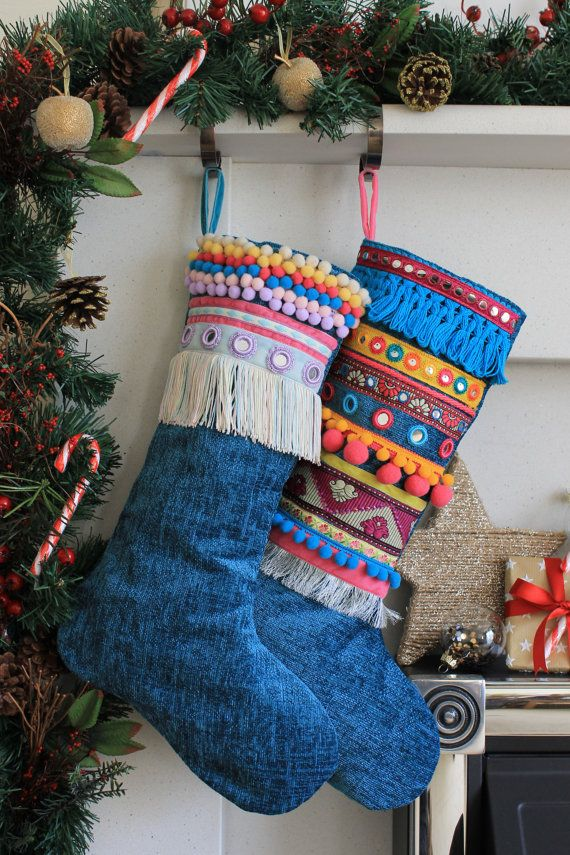 Decorative festive stocking made from a teal blue coloured chenille velvet fabric embellished with various trims.  A beautiful stocking to hang from your mantelpiece over the festive period. Each embellished stocking is one-of-a-kind and unique. This one features lilac crocheted shisha mirrors, pom pom trims, fringing,velvet ribbon and embroidered trim.  Fully lined with a lilac cotton fabric and finished with a velvet hanging loop.  Length : 39 cm Width : 16 cm (across cuff)  25 cm (across…