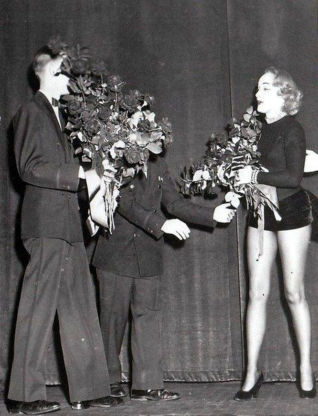 Marlene Dietrich, receiving flower's from an admirer.