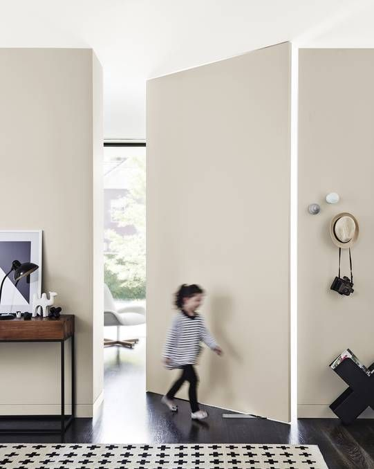 Dulux Whisper White on the ceiling, White Duck adds continuity to the swivel door and walls. Photo: Dulux.