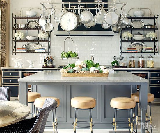 With a flair for the dramatic and a love of the romantic, this kitchen combines Directoire style with modern furnishings. Wall-mount shelves and a suspended pot rack provide practical counterpoints to the kitchen's cool perimeter cabinets and architectural granite-top island./