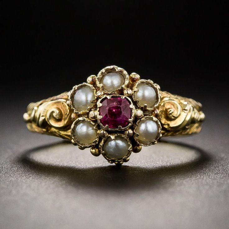 This exquisite little Victorian jewel features a ruby-centered, pearl-petaled flower further ornamented with tiny granulation work and fancy repousse shoulders. Delicately crafted in 18K yellow gold and as sweet as can be from the mid-to-latter 1800s.