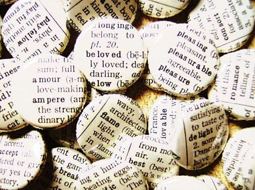 Buttons covered with pieces of an old dictionary each featuring a romantic word . . . i feel a DIY coming on!
