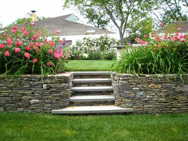Garten gestalten Hang Lage Stützmauer Rasen Stein Frühlingsblumen