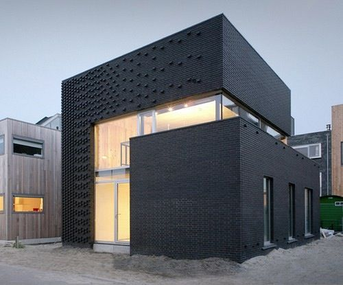 Really cool all black brick exterior on this modern home Designed by Marc Koehler