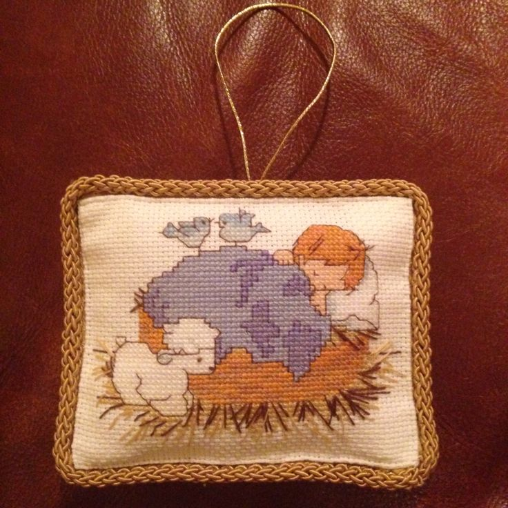 Baby Jesus in manager with lamb Christmas ornament.