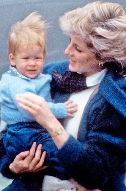 Prince Harry cuddles by his mother Princess Diana while arriving at a blustery Aberdeen Airport in September 1985