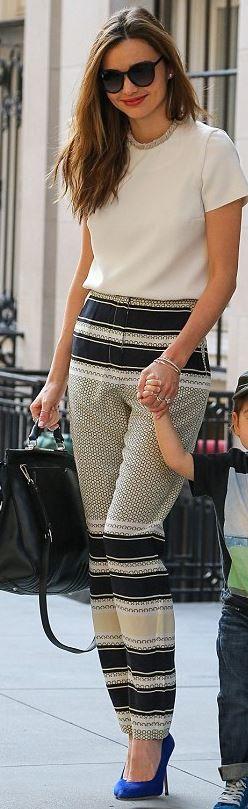 Who made  Miranda Kerr's black handbag, white tee, black sunglasses, print stripe pants, and blue suede pumps that she wore in New York?