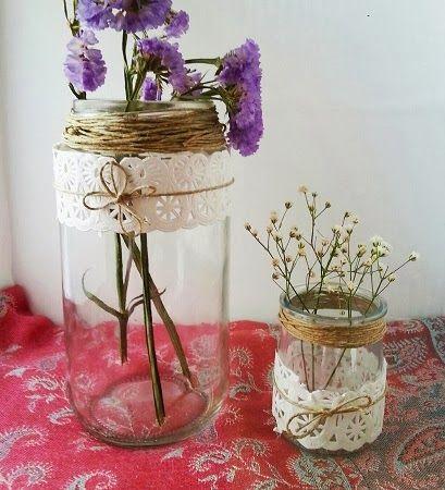 Botes de cristal como románticos floreros con blondas y cuerda de yute