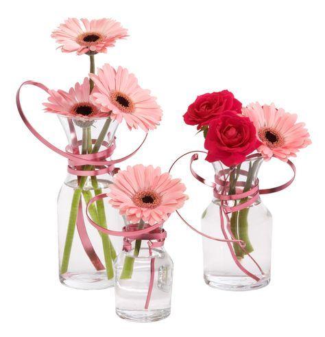 roze gerbera's in glazen vaasjes