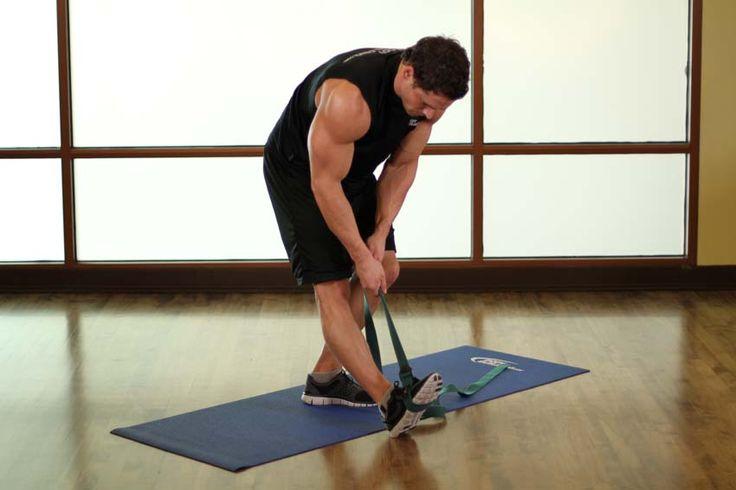Растяжка мышц голени и задней поверхности бедра в положении стоя — техника выполнения упражнения:  Накиньте ремень, эспандер или канат на ступню. Выставьте эту ногу немного вперед. Нога впереди остается прямой, опорную согните. Поднимите носок ноги, стоящей впереди, с пола и потяните его на себя. Используя ремень, тяните носок на себя, увеличивая натяжение, растягивая мышцы. Задержитесь в этом положении на 10-20 секунд, затем повторите растяжку другой ногой.