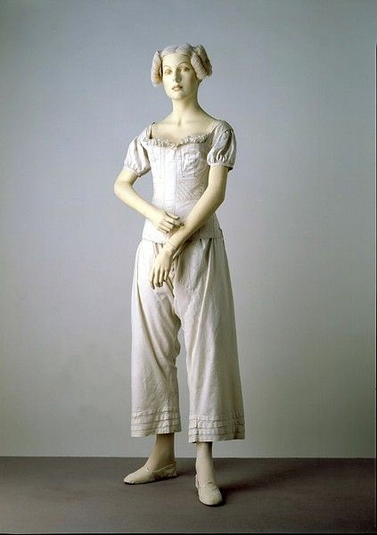 1834 This ensemble illustrates the items of underwear worn by women in the 1830s. The shift had been an essential element of underwear for centuries. When the sheer fabrics and rather clinging styles of Neo-classical dress became fashionable, drawers were introduced into the female wardrobe for modesty. The corset is lightly boned and reinforced with cording. There is a long narrow pocket in the front for the busk, a wide piece of wood or ivory, which kept the corset stiff and flat in front.