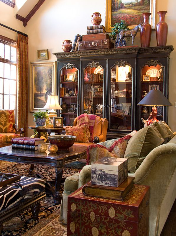 Gary Riggs Website: So warm and inviting in spite of the high ceilings.   By decorating on top of, and above the cabinet, they visually brought down the height of the ceiling which makes it feel cozier.  I love the lights in the cabinet as well.  Just beautiful!