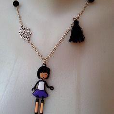 Sautoir composé d'une jolie petite poupée, montée sur une chaine argentée agrémentée de perles et d'un pompon