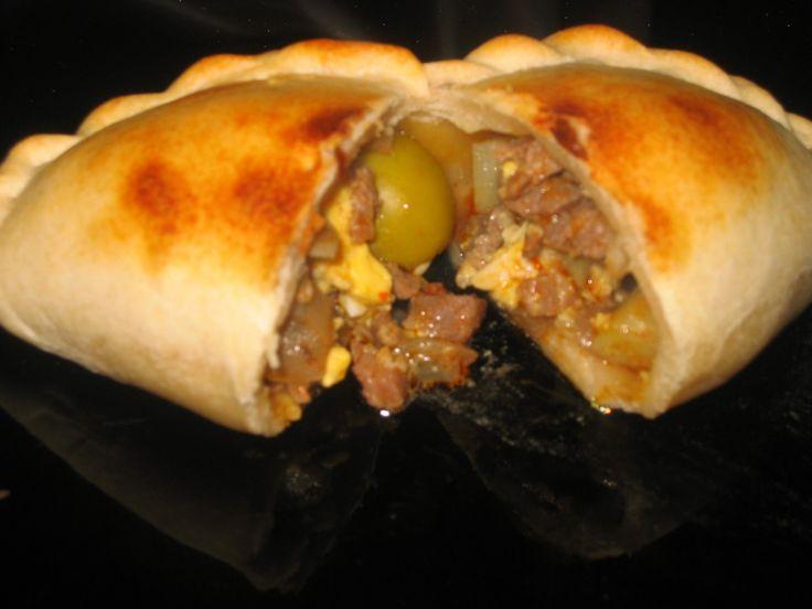 Empanada de horno, lleva carne picada, cebolla, huevo duro, aceitunas y pasas