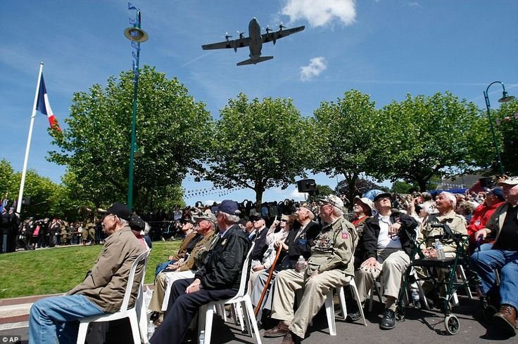 Fly-by: US WW II veterans look at a C130 Air Force plane, which flies above Sainte-Mere-Eg...