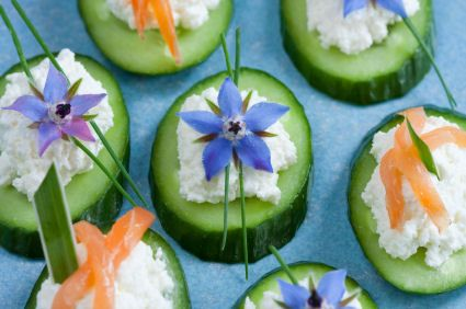 Cucumber with edible flowers Canapés - goat cheese and ricotta spread on a cucumber slice are garnished with chives and a borage blossom.