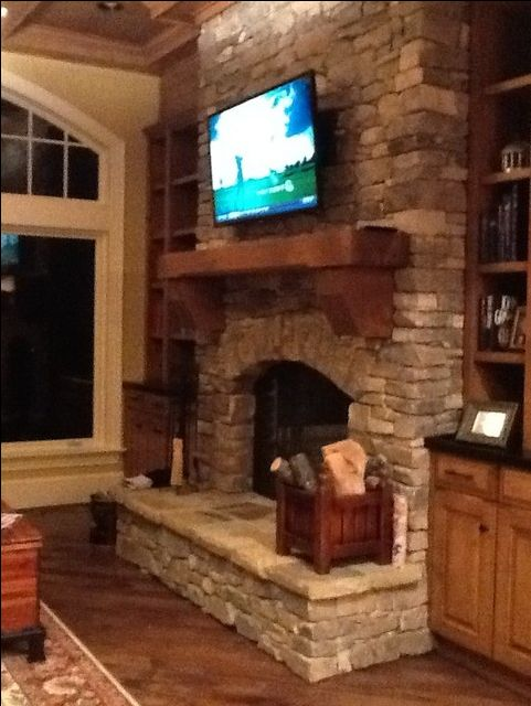 I like the rough wood mantel and the tv mounted over the fire place.. Now all it needs is a nice rustic wooden cabinet to hide the tv when it's not in use!