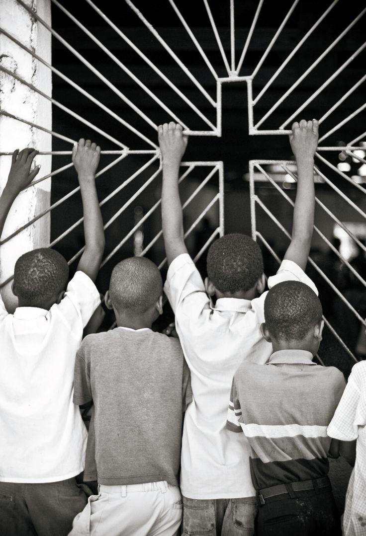 매달림 | 아이티, 2005 | 데이비드 두쉬민 매달림'은 비정부기관(NGO)과 관련한 내 첫 번째 프로젝트의 일환으로, 어느 일요일 아침 아이티에 있는 한 교회 밖에서 촬영한 것이다. 교회 안에 더 이상 자리가 없어서 밖에서 예배를 지켜보고 있는 소년 네 명을 2:3 세로 프레임으로 찍은 것이다.