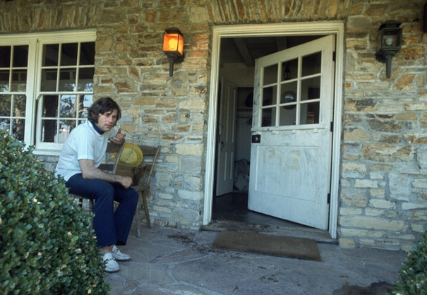 """August 1969: Roman Polanski sits in disbelief on the bloodstained porch at 10050 Cielo Drive, where his pregnant wife, Sharon Tate, and four others were butchered just nights before. The word """"PIG"""" is clearly visible on the door, scrawled in Tate's blood."""
