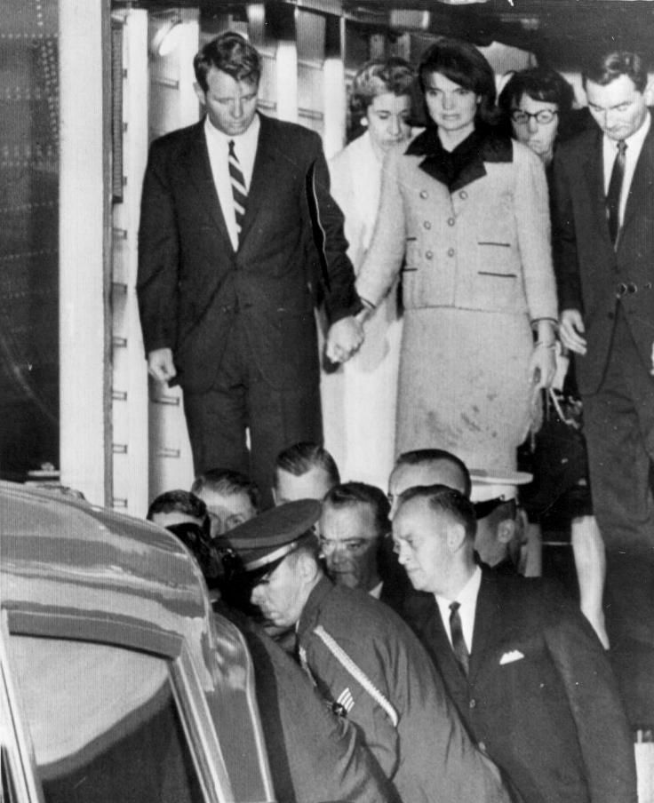 kennedys:  An equally disturbed Attorney General and brother-in-law Robert F. Kennedy escorts Mrs. Kennedy off of the plane and into history - the remnanets of the dream-like post-war era of Camelot halts to an end.