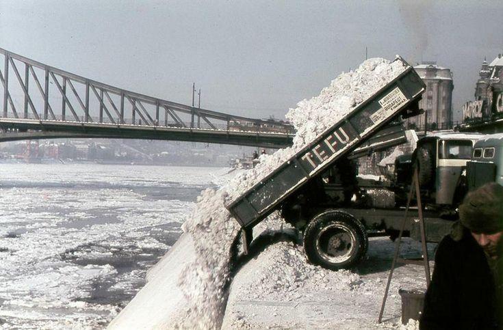 1960-as évek. Budapesti TEFU teherautók borítják a Dunába a városból eltakarított havat a Szabadság-híd mellett