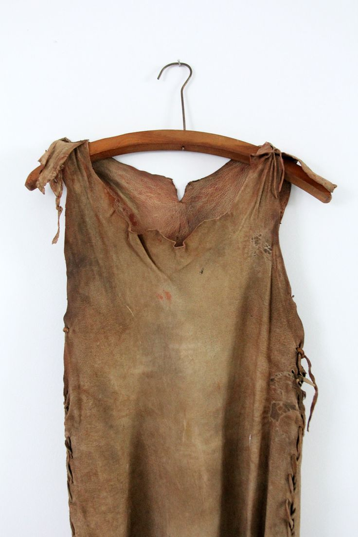 Beautifully aged, this is a vintage Native American dress. Buckskin leather shapes the dress with hand-stitched seams and ties up the sides and at the shoulders. Wapum or shells adorn the dress, and i
