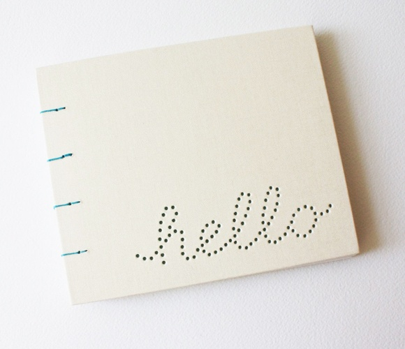 Hand-punched the word *hello* in the front cover, which is covered with off white bookcloth. the inside front cover is butcher paper, and shows through the holes in the front. Available in: white, pink, blue, aqua.