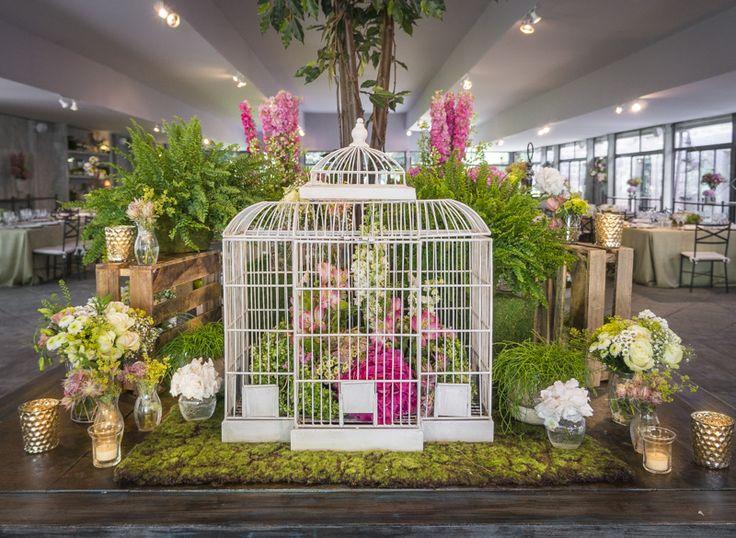 frontal bodegn mesa hall base de musgo con jarrones de flores jaula y velas