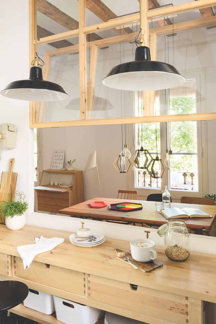 Cocina y comedor comunicados a través de pasaplatos con ventana de madera y cristal con cuarterones