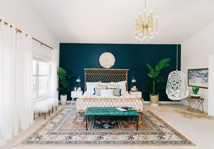 Gorgeous master bedroom with midnight blue feature wall, mod lighting, deep teal bench at foot of bed, layered rugs. The swinging chair might be too much for my little bedroom...