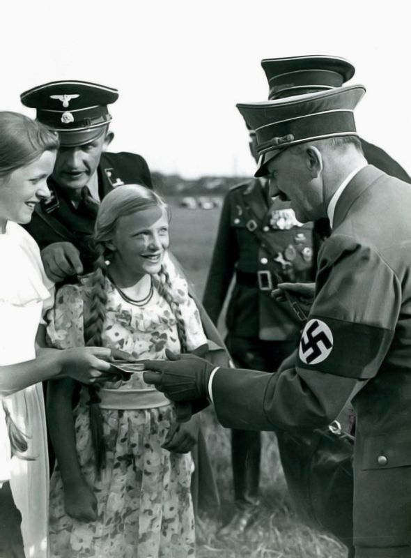 Hitler signing autographs with his valet, Krause, behind.