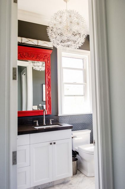 Painted a raw-wood mirror from Bali a vivid orange-red. The sleek wall sconce above is Robert Abbey's Chase Bath Strip, from YLighting.